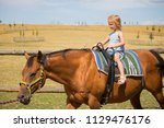 a young girl walks on a trained ... | Shutterstock . vector #1129476176