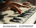 small hands playing keyboard | Shutterstock . vector #1129500569