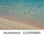 beach sand and blue ocean water ... | Shutterstock . vector #1129504850