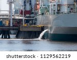 a tanker discharging ballast.... | Shutterstock . vector #1129562219