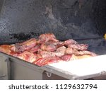 smoked meats on a grill waiting ... | Shutterstock . vector #1129632794