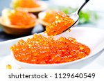 Small photo of Red Caviar in a spoon. Caviar in bowl. Close-up salmon caviar. Delicatessen. Gourmet food. Texture of caviar. Seafood.