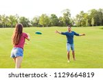 couple in love playing frisbee... | Shutterstock . vector #1129664819
