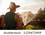 mature woman gardener watering...   Shutterstock . vector #1129672409