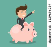 businessman riding piggy bank... | Shutterstock .eps vector #1129696259
