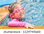 little girl at the edge of pool | Shutterstock . vector #1129745660