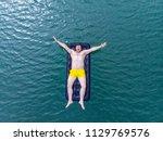 man on mattress in blue water.... | Shutterstock . vector #1129769576