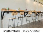 Stock photo empty on people coffee shop interior design with chairs and white walls 1129773050