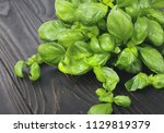 fresh green basil on a dark... | Shutterstock . vector #1129819379