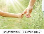 hands of parent and child in... | Shutterstock . vector #1129841819