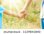 hands of parent and child in... | Shutterstock . vector #1129841840