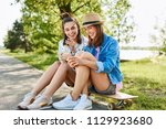 young women sitting on... | Shutterstock . vector #1129923680