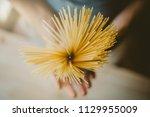 man holding italian uncooked... | Shutterstock . vector #1129955009