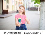 Small photo of A girl in a pink T-shirt and a bright multi-colored skirt is holding ice cream in a green horn. Ice cream and hand show class, delicious
