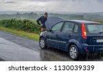 car trouble in the rain. broken ... | Shutterstock . vector #1130039339