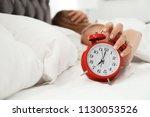 woman turning off alarm clock... | Shutterstock . vector #1130053526