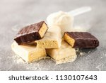 Stock photo whey protein powder in measuring scoop and different energy protein bar on black background 1130107643