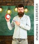 teacher in eyeglasses holds... | Shutterstock . vector #1130145314
