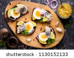 Stock photo sandwich on bread with herring potatoes egg onion tasty appetizer with mustard on the board 1130152133
