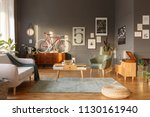 Real photo of an interior of entertainment room with vintage furniture like sofa with a blanket, comfortable armchair, small coffee table and footrest on green rug - stock photo