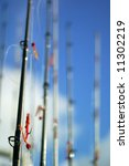 A group of fishing poles ready for use, against blue cloudy sky - stock photo