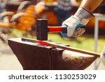 a blacksmith hammering a hot... | Shutterstock . vector #1130253029