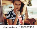 young caucasian woman drinking... | Shutterstock . vector #1130327456