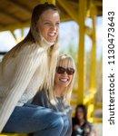 two cute young women smiling...   Shutterstock . vector #1130473643