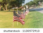 long row of lawn american flags ... | Shutterstock . vector #1130572913