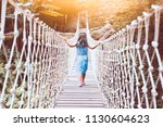 Cute asian child girl walking on the hanging rope bridge across the river in the forest with fun