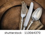 Vintage silverware on rustic wooden plate - stock photo