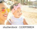 pretty young woman mother holds ... | Shutterstock . vector #1130958824