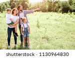 Nice picture of family standing together on meadow. Mom is holding her son on hands. Girl is standing besides her parents. Guy is pointing down further.