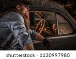 Caucasian Cowboy Classic Cars Collector. Portrait of Men and Old Rusty Vehicle Inside the Barn. - stock photo