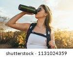 woman taking a break to drink... | Shutterstock . vector #1131024359
