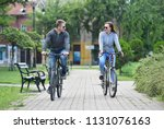 young couple riding bicycle... | Shutterstock . vector #1131076163