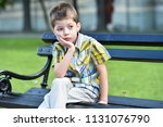sad child boy sitting on a bench | Shutterstock . vector #1131076790