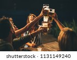 Stock photo group of friends drink beer on the terrace and toast during summer night 1131149240
