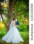 groom embraces bride's waist ... | Shutterstock . vector #1131210200