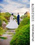 groom holds hand of beautiful... | Shutterstock . vector #1131210278