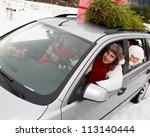 Christmas shopping - the family is riding a car with christmas tree and gifts on the roof of the car