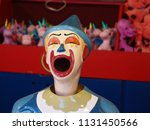Small photo of Old Fashioned Vintage Carnival Laughing Clown in Strong Lurid Colors.
