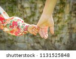 the parent holds the hand of a... | Shutterstock . vector #1131525848