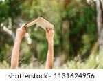 hands raising a book up to read   Shutterstock . vector #1131624956
