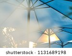 a beach umbrella blocks out the ... | Shutterstock . vector #1131689198