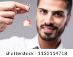 smiling man holding up a key... | Shutterstock . vector #1132114718