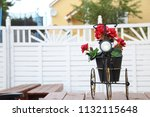 bicycle carrying red flowers in ... | Shutterstock . vector #1132115648