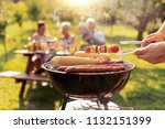 happy family barbecuing meat on ... | Shutterstock . vector #1132151399