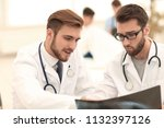 two doctors looking at x ray. | Shutterstock . vector #1132397126