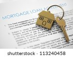 Mortgage loan agreement application with house shaped keyring - stock photo